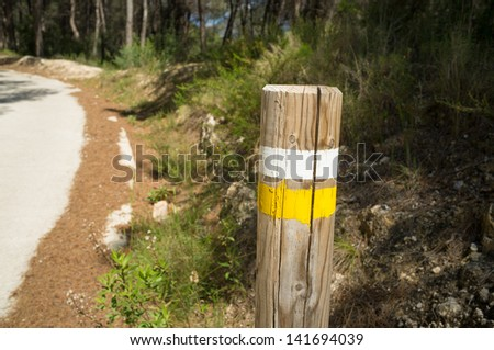 Hiking trail marking on a wooden pole along the way - stock photo