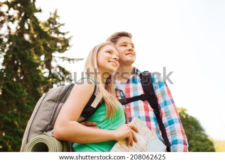 hiking, travel, vacation and friendship concept - smiling teenage couple with map and backpack in nature