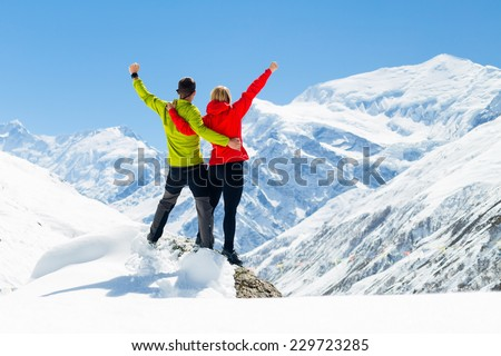 Hiking woman and success in mountains. Fitness and healthy lifestyle outdoors in winter nature - stock photo