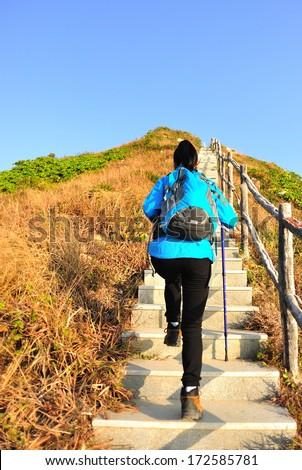 hiking woman climbing mountain stairs  - stock photo
