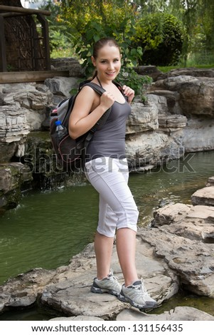 Hiking woman cross river with travel bag. Beautiful young Caucasian sporty woman travel in mountains