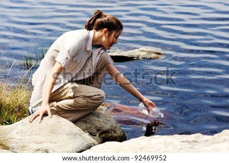 hiking woman fills up her water bottle in a fresh water lake - stock photo