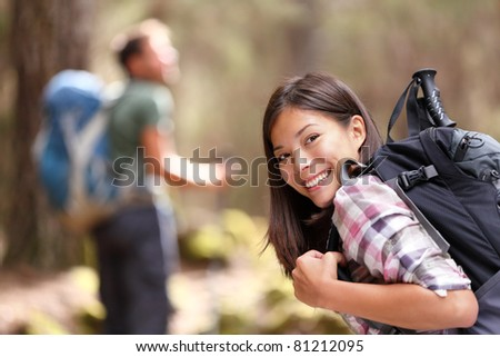 Hiking. Woman hiker smiling in forest with male hiker in the background. Mixed-race Asian Caucasian female model happy. From Aguamansa, Tenerife, Spain - stock photo