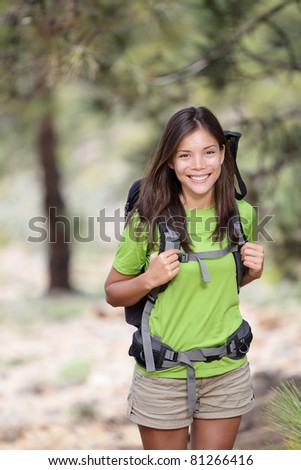 Hiking. Woman hiker smiling standing outside in forest with backpack. Outdoors portrait of happy beautiful young asian woman model - stock photo