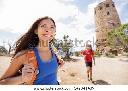 Hiking woman in grand canyon. Female hiker smiling happy with boyfriend in background during hike trekking at South Rim, Desert View Watchtower, Arizona, USA. Couple living healthy liifestyle. - stock photo