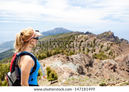 Hiking woman in mountains. Female hiker looking at beautiful view. Fitness and healthy lifestyle outdoors in summer nature, Canary Islands - stock photo