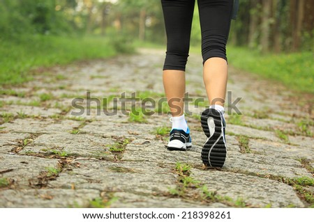 hiking woman legs walking on forest trail  - stock photo