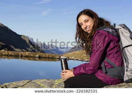 Hiking woman making a pause on mountain - stock photo