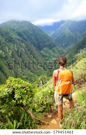 Hiking woman on Hawaii, Waihee ridge trail, Maui, USA. Young female hiker walking in beautiful lush Hawaiian forest nature landscape in mountains. Asian woman hiker wearing backpack looking at view. - stock photo
