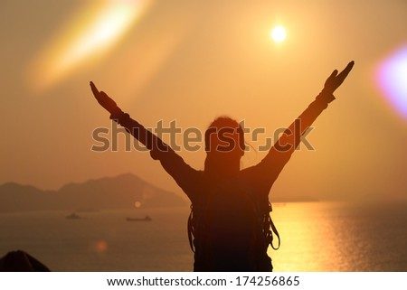 hiking woman open arms to the sunrise stand at seaside mountain - stock photo