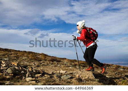 Hiking woman over blue sky, Nordic Walking in Autumn mountains - stock photo