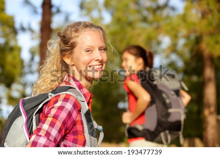 Hiking woman portrait smiling happy in forest. Female hiker girl trekking wearing backpack outside looking candid and fresh at camera. Beautiful young blonde girl living healthy lifestyle. - stock photo