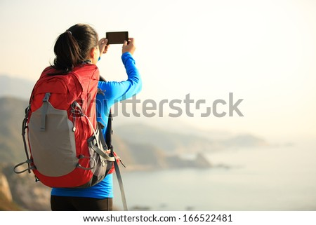 hiking woman use smart phone taking photo - stock photo