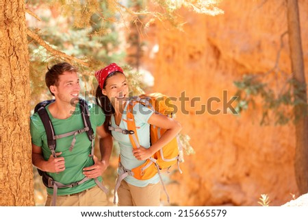 Hiking - young couple of hikers relaxing resting in Bryce Canyon walking smiling happy together. Multiracial couple, young Asian woman and Caucasian man in Bryce Canyon National Park landscape, Utah - stock photo