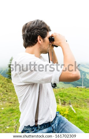 Hiking - Young man in the Bavarian Alps looking through a field glasses or binocular enjoying the panorama in the leisure time or vacation - stock photo