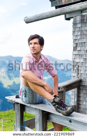 Hiking - Young man sitting at mountain hut in the Bavarian Alps and enjoys the panorama in the leisure time or in vacation - stock photo