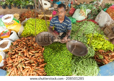 HIKKADUWA, SRI LANKA - FEBRUARY 23, 2014: Portrait of vendor selling his produce. The Sunday market is great way to see Hikkaduwa's local life come alive along with fresh produce and local delicacy - stock photo