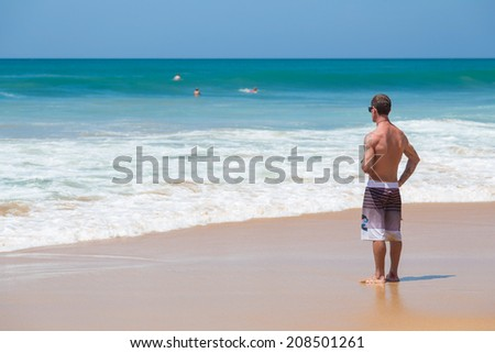 HIKKADUWA, SRI LANKA - FEBRUARY 24, 2014: Surfer checking out waves on the horizon. Hikkaduwa is well known tourist international destination for board surfing. - stock photo