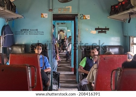 HIKKADUWA, SRI LANKA - MARCH 12, 2014: Commuters sitting in train to Colombo. Trains are very cheap and poorly maintained but it's the best option to witness a bit of everyday local life. - stock photo