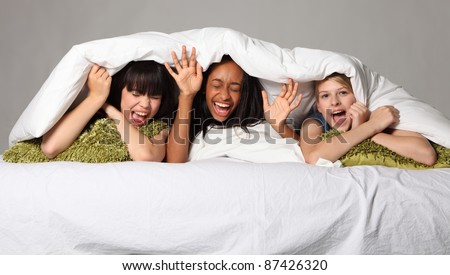 Hilarious fun and scream with laughter at sleepover party for three happy beautiful teenage girl friends, a mixed race african american, oriental Japanese and blonde caucasian school mates. - stock photo