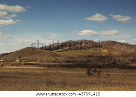 Hill and the yellow field on a clear day. Early spring, autumn. Landscape.