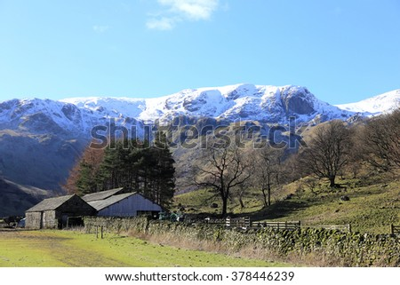 Hill Farm near Patterdale in the Lake District National Park in February with the snow covered Rydal Fells behind. - stock photo