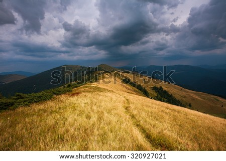 Hill in the mountains on the background of dramatic sky and storm clouds - stock photo