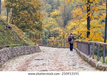 Hill near the central square of Vilnius in Lithuania. Girl climbs top along road covered with paving stones - stock photo