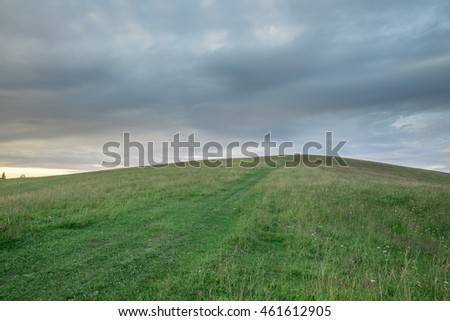 Hill with green grass and pathway against the sky with storm clouds at sunset