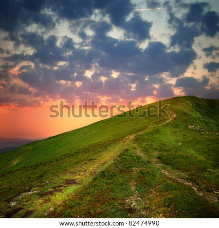 hill with pathway and clouds on sky in sunset time - stock photo