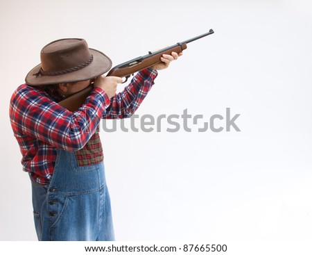 hillbilly farmer taking aim with his gun. - stock photo
