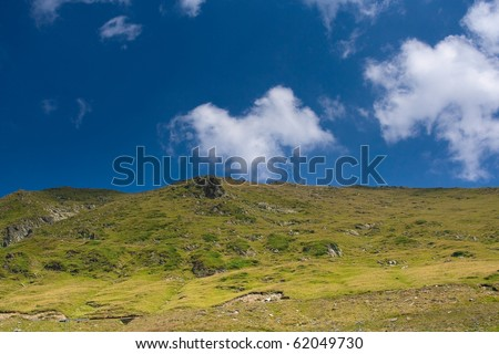 hills and blue sky with clouds on horizon - stock photo