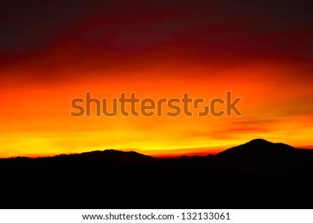 Hills and bright sky during sundown - stock photo