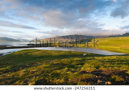 Hills covered with green grass and lakes in West Iceland on a cloudy day - stock photo