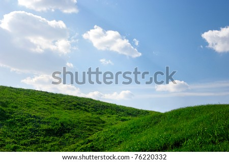 Hills covered with green grass under blue sky Summer landscape background - stock photo