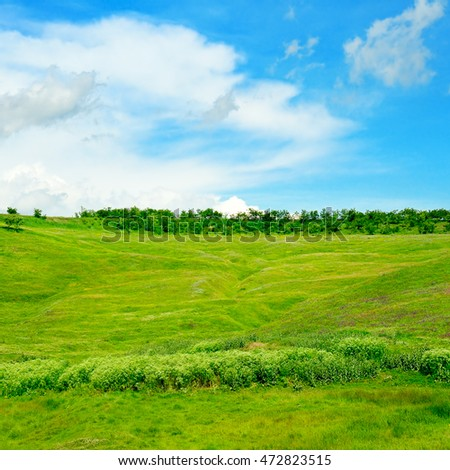hills, green grass and blue cloudy sky