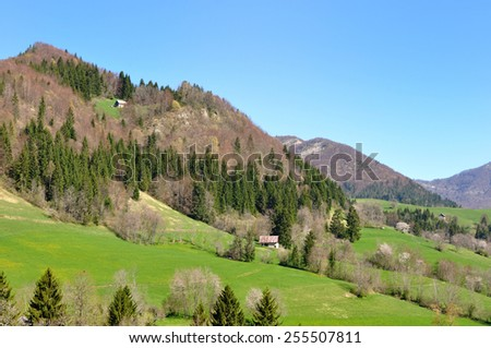 hills in greenery landscape with a house under blue sky - stock photo
