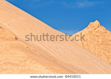 hills of sand and stone of a mine gives an impression of mountains - stock photo