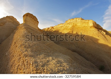 Hills of soft picturesque forms from sandstone on a sunset