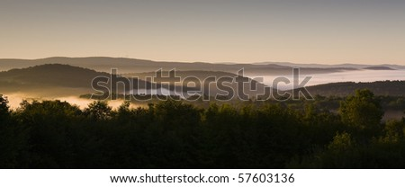 Hillside forests with low lying fog in the valleys at dawn. Horizontal shot.