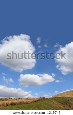 Hillside in spring, set against a blue sky with clouds. Set in the Brecon Beacons National Park, Wales, United Kingdom. - stock photo
