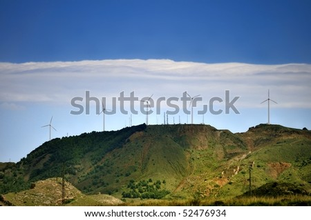 Hillside of La Sierra Mineria at La Union, near Cartagena, Spain. Disused mine works are nestled into the hillside and the hill is topped with wind turbines and communications masts. - stock photo