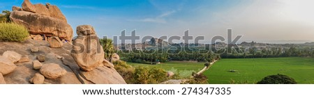 Hilltop view of Hampi's boulder strewn landscape and rice paddies - stock photo
