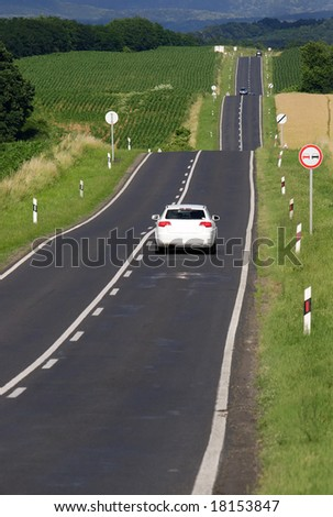 Hilly asphalt road with white car and beauty landscape - stock photo