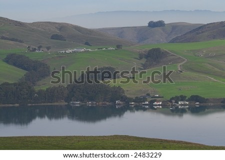 Hilly lakeside pastures with farm houses - stock photo