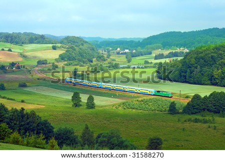 Hilly landscape with a railway line, long train, lake and forests during the summer day