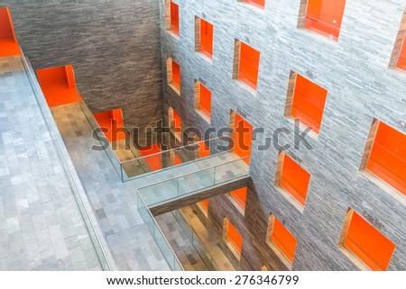 HILVERSUM, THE NETHERLANDS - MARCH 03: Modern interior Dutch institute Sound and Vision with several floors and orange painted passages on March 03, 2015 in Hilversum, The Netherlands - stock photo