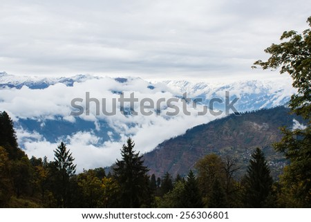 himalayan mountains covered with clouds in overcast weather - stock photo