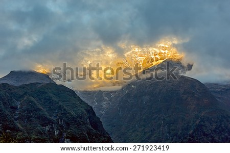 Himalayan peak near Thame village in the clouds at sunset - Everest region, Nepal - stock photo