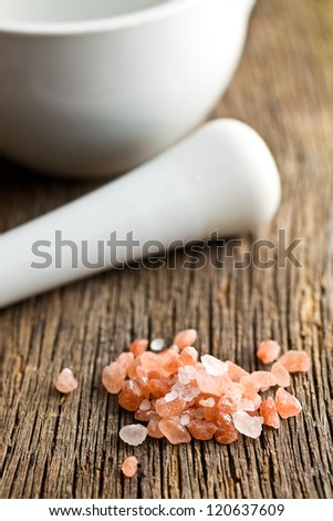 himalayan pink salt on kitchen table - stock photo